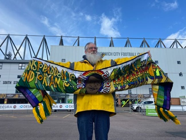 David Shenton outside carrow road with the football scarf he has created