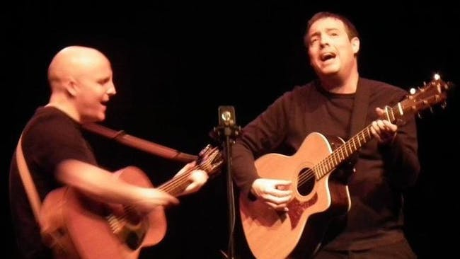 Two men playing guitars and singing into a microphone