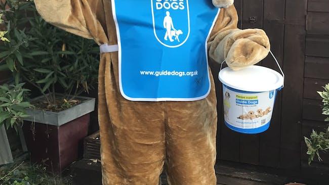 A Guide Dogs mascot waving