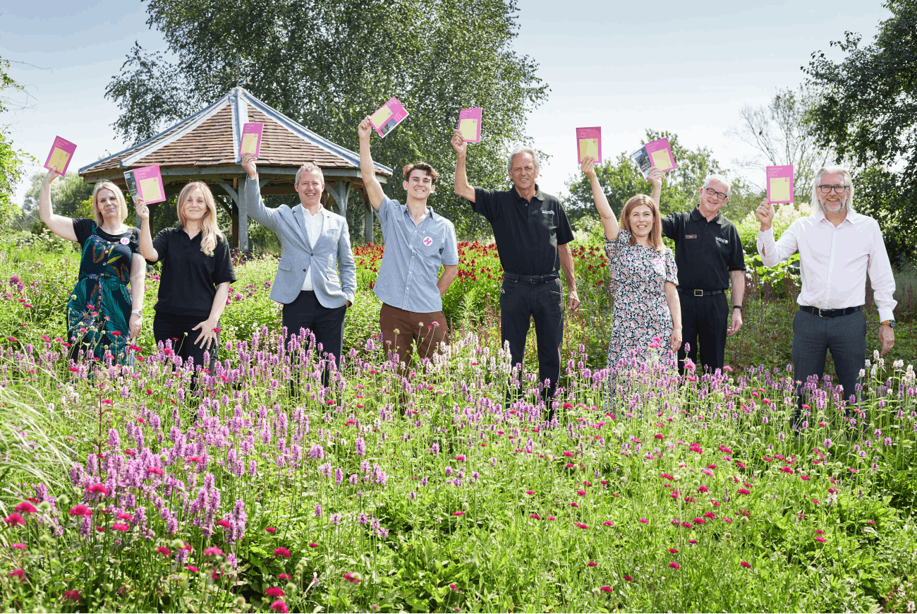 Members of the Norfolk Heritage Open Days and Pensthorpe team hold up the 2021 brochure in a park full of flowers.