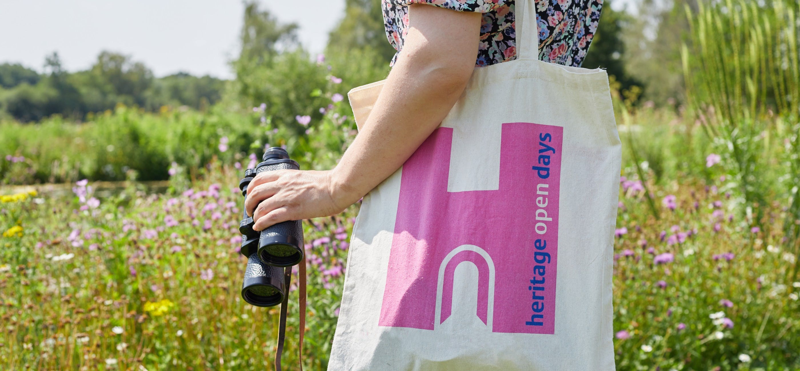 Close up of a person carrying a Heritage Open Days bag and a pair of binoculars with a field of flowers in the background.