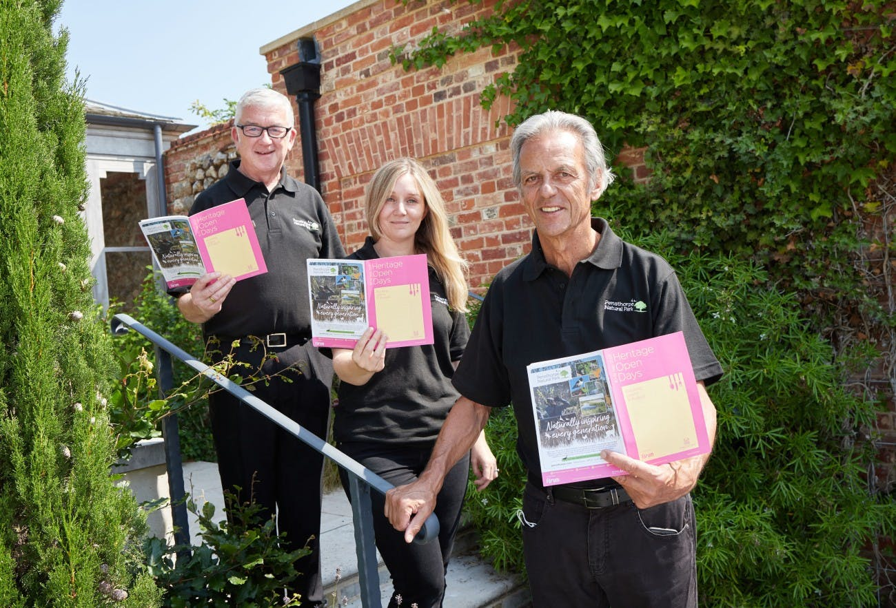 Members of the Pensthorpe Natural Park team holding the Heritage Open Day brochure.