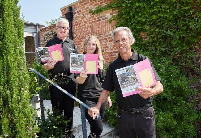 Members of the Pensthorpe Natural Park team hold up the Norfolk Heritage Open Days brochure.