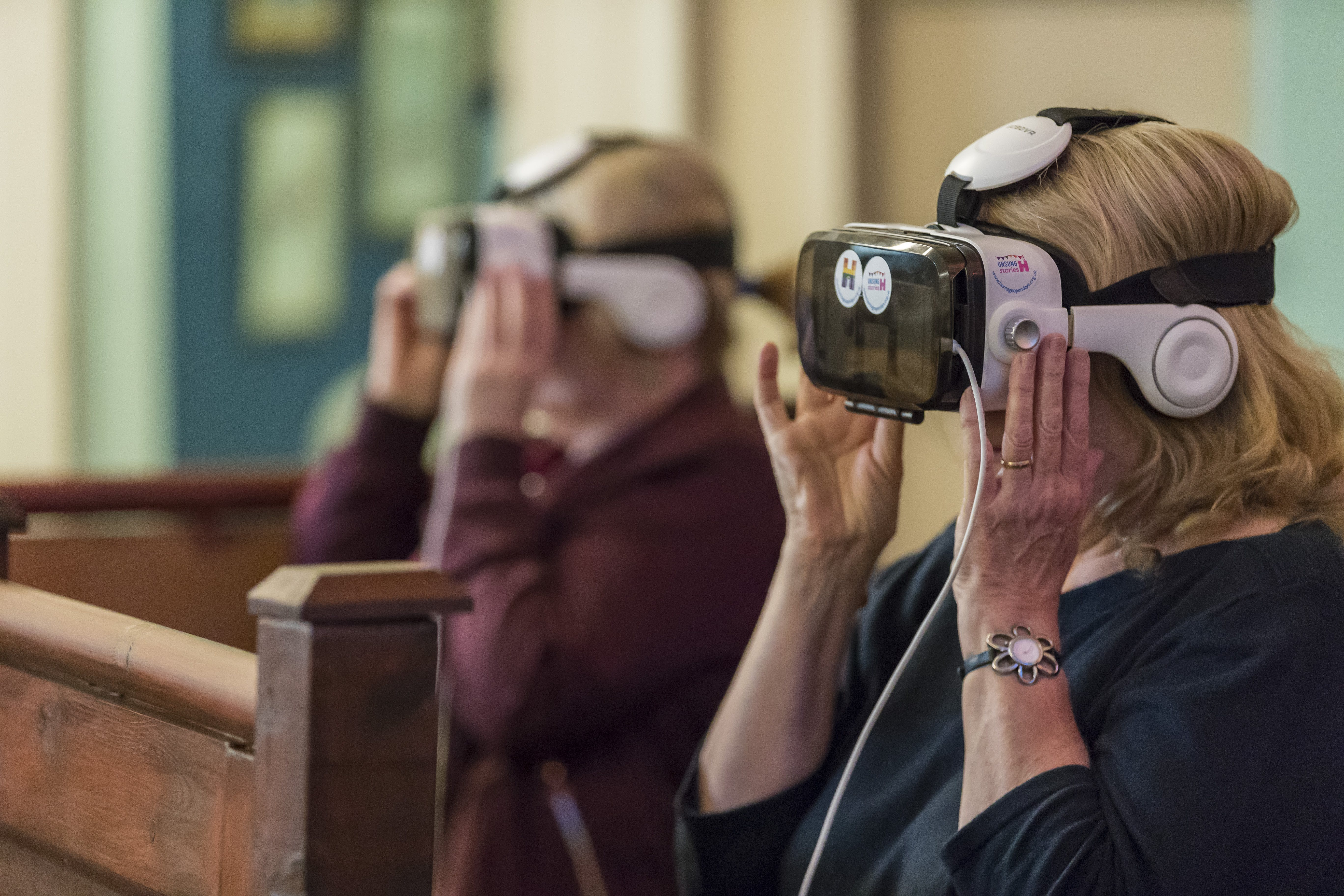 People viewing an event through Heritage Open Days branded VR goggles