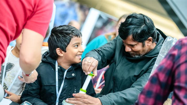 A boy looks at his father smiling while he does a science experiment