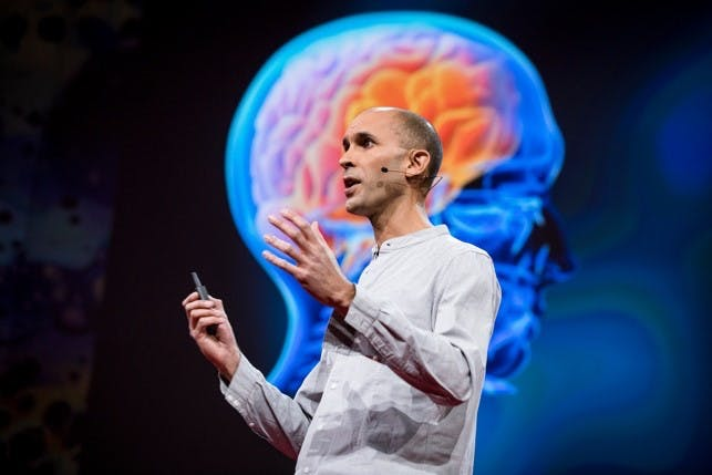 Image of Anil Seth speaking with an image of the human brain behind.