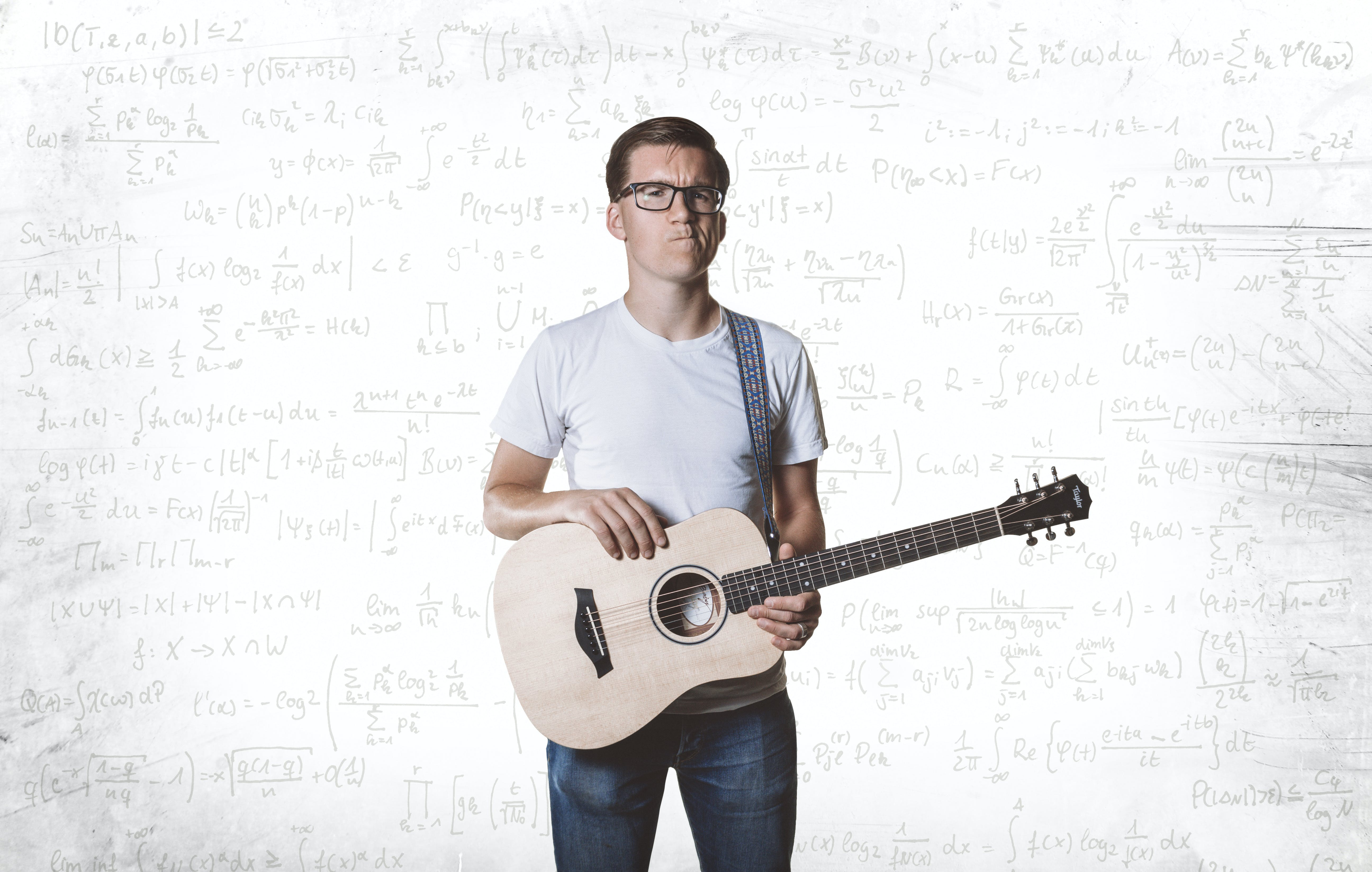 Kyle Evans holding his guitar in front of a white wall covered with mathematical equations.