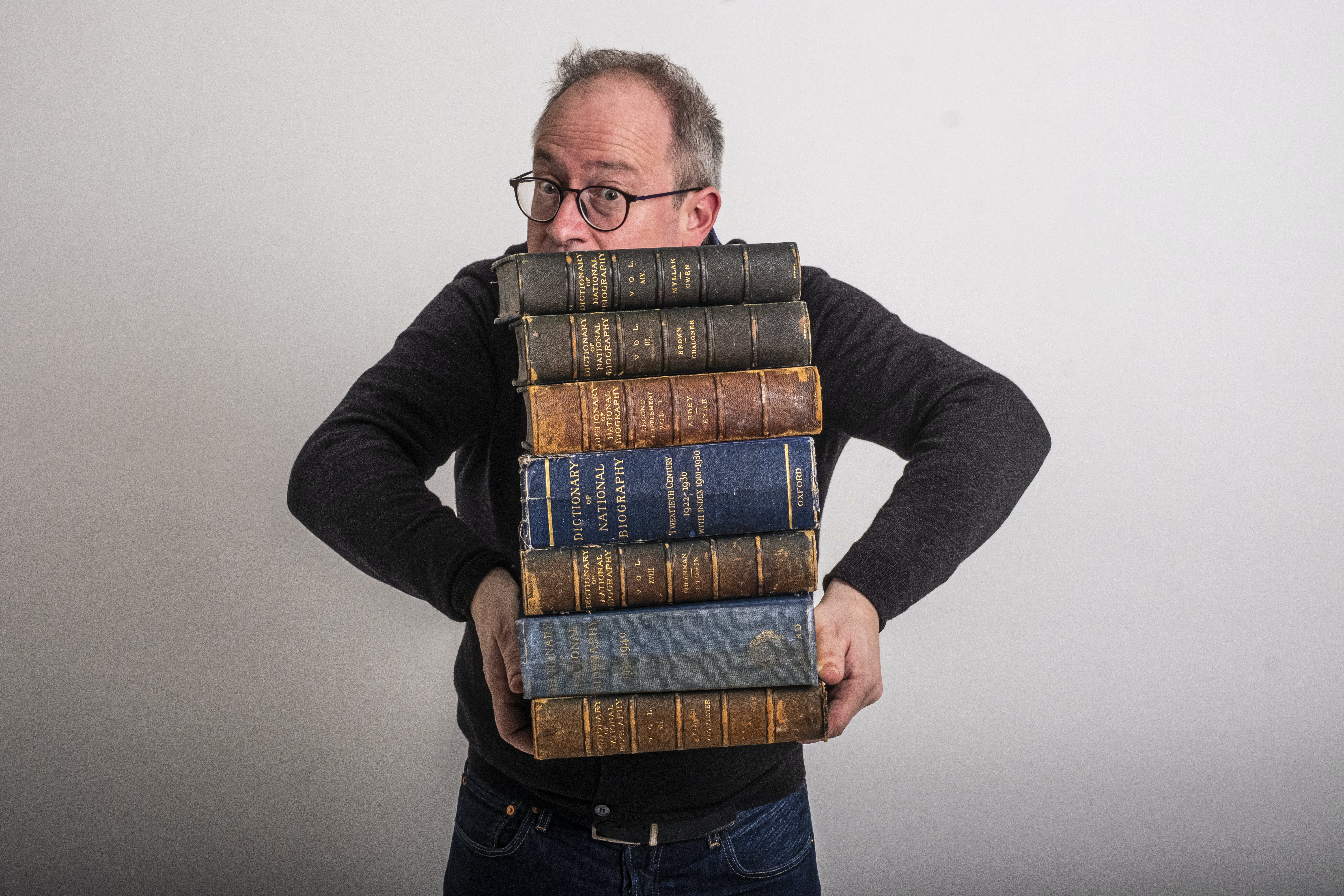 Robin Ince holding a big stack of old books.