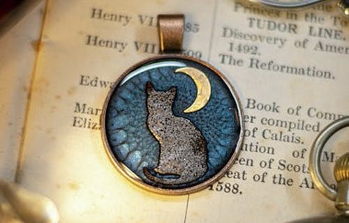 A necklace with a cat and the moon made by Jabbawockycrafts