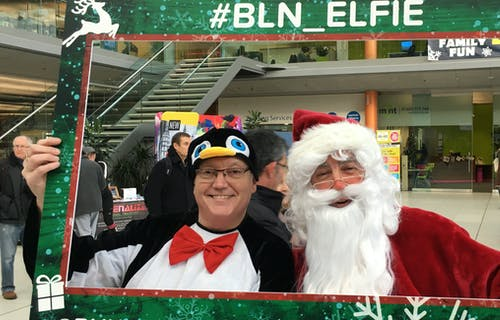 Two people take a selfie in a festive photo frame, one is dressed as a penguin, one as Father Christmas
