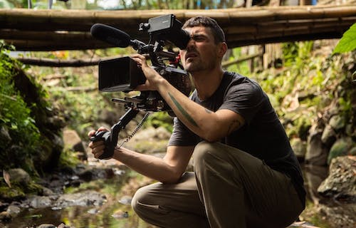 Image of Dan O'Neill with video camera recording something out of view. Dan is crouched down in a forest setting.