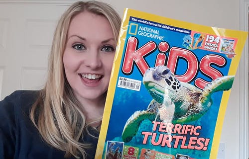 Kate Stephenson holding a Kids edition of National Geographic magazine.