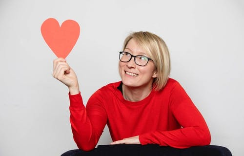 Laura Mucha wearing a red cardigan and smiling at a red paper heart in her hand.