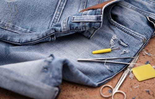 A pair of jeans ready to be mended with scissors and thread.