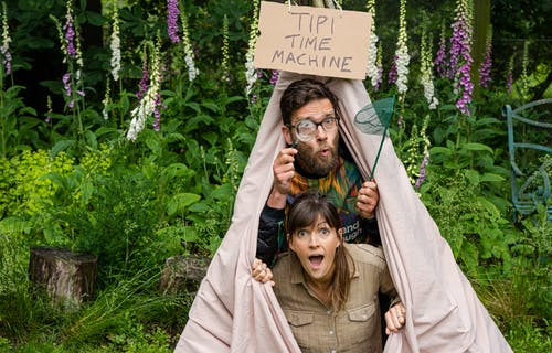 Image of Theo Blossom and Jess French in a Tipi labelled the Tipi Time Machine. Theo is holding a magnifying glass and butterfly net,