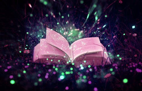 Image of open book in grass and dark setting surrounded by glowing green and pink lights
